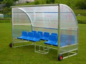 Freestanding team shelter aluminium construction, portable on wheels, seats in 2 rows, cell-like polycarbonate panels.